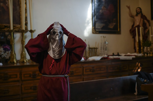 A member of La Hermandad de Jesus Brotherhood prepares his clothes, prior to the Station of the Cross service on Good Friday after congregation numbers were reduced, due to the coronavirus pandemic, in Pamplona, northern Spain, Friday, April 2, 2021. (Photo by Alvaro Barrientos/AP Photo)