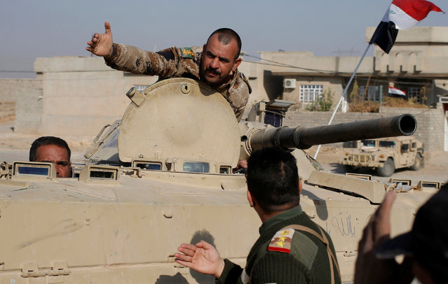 An Iraqi soldier gestures from an armoured vehicle during clashes with Islamic State fighters in Al-Qasar, South-East of Mosul, Iraq November 28, 2016. (Photo by Goran Tomasevic/Reuters)