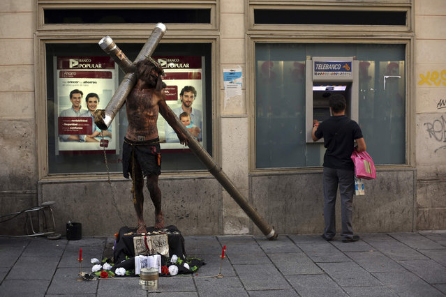 A performer dressed as Jesus Christ stands next to a man using an ATM machine in Madrid September 4, 2013. Spain's economy has been in recession since mid-2011, the second since a decade-long property bubble burst in 2008, though the government has said it expects to see quarterly growth in the second half of 2013. (Photo by Susana Vera/Reuters)