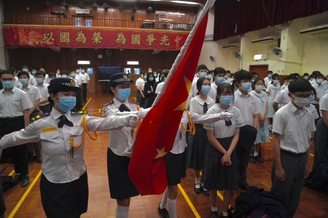 """Students attend a flag raising ceremony during the National Security Education Day at a secondary school, in Hong Kong, Thursday, April 15, 2021. Beijing's top official in Hong Kong on Thursday warned foreign forces not to interfere with the """"bottom line"""" of national security in Hong Kong, threatening retaliation even amid ongoing tensions between China and Western powers. (Photo by Kin Cheung/AP Photo)"""
