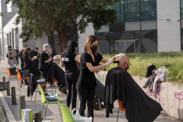 Hairdressers of Thessaloniki provide haircuts to homeless people outside of a shelter for the homeless in Thessaloniki, northern Greece, 28 April 2021. (Photo by Nikos Arvanitidis/EPA/EFE)