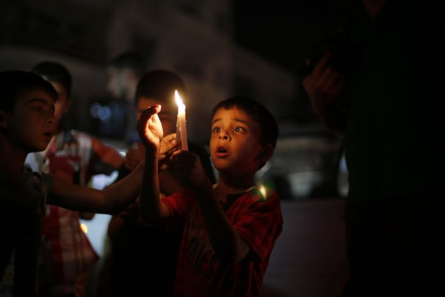 Palestinian children light candles during a protest against power cuts and the blockade on the Gaza Strip, in Gaza September 19, 2013. Israel imposed a blockade on Gaza in 2007 after its enemy, Islamist group Hamas, seized control of the territory in a brief civil war with Western-backed Palestinian President Mahmoud Abbas's Fatah party. (Photo by Suhaib Salem/Reuters)