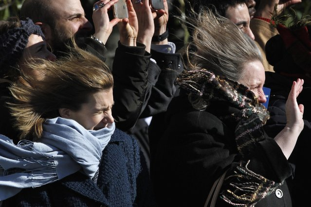 Women wave as their hair and scarves are blown in the wind from the Marine One helicopter as President Barack Obama leaves the South Lawn of the White House in Washington, Wednesday, January 13, 2016, for a short trip to Andrews Air Force Base, Md., then onto Nebraska and Louisiana. (Photo by Jacquelyn Martin/AP Photo)