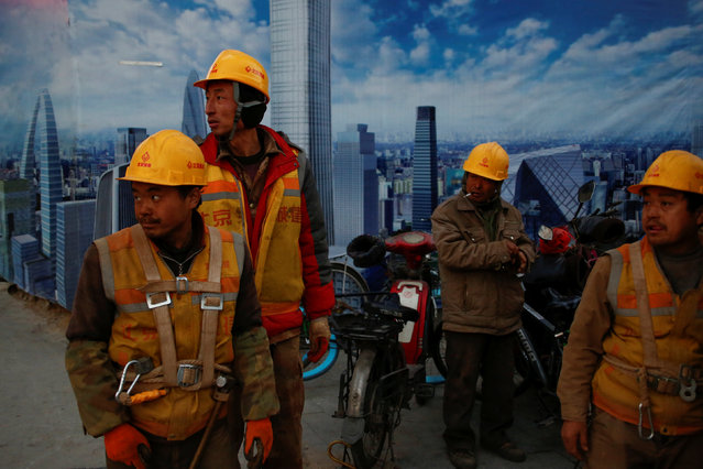 Workers stand outside a construction site at the end of their shift in Beijing, China December 6, 2016. (Photo by Thomas Peter/Reuters)
