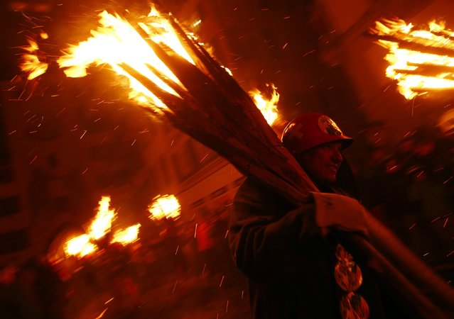 Carnival revellers carry burning wooden sticks during the traditional Swiss Chienbaese celebration in Liestal near Basel February 22, 2015. (Photo by Ruben Sprich/Reuters)