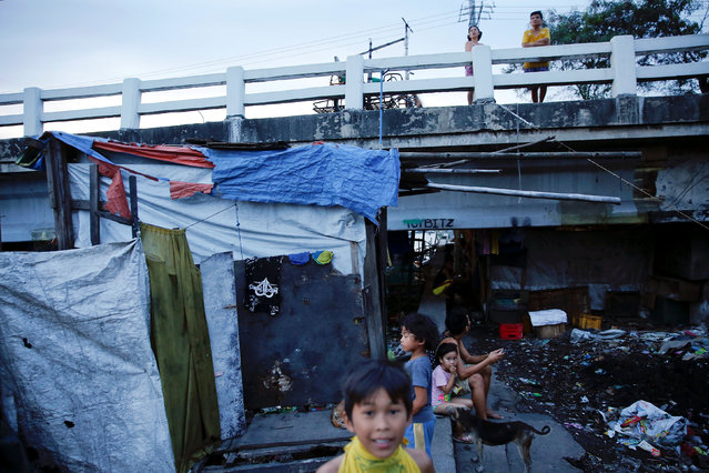 People pass the time under C-3 bridge in North Bay Boulevard South (NBBS), a Navotas City district of slums and waterways with a high number of drug war deaths, in Manila, Philippines November 3, 2016. (Photo by Damir Sagolj/Reuters)