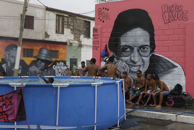 A group of friends take a break from swimming, backdropped by a mural featuring Salsa singer Hector Lavoe, in Callao, Peru, Sunday, February 22, 2015. Local officials say the pools often block traffic and that stagnant water can become a breeding ground for disease-carrying mosquitoes. (Photo by Martin Mejia/AP Photo)