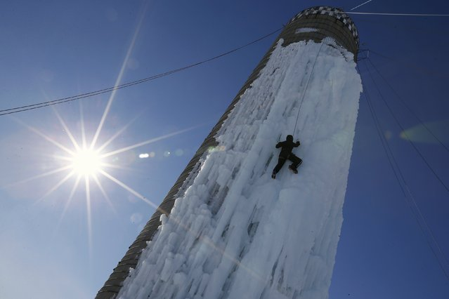 An climber ascends a silo covered in ice in Cedar Falls, Iowa, United States, January 17, 2016. The owners have connected hoses to the top of the silo and spray it with water in winter months to freeze the exterior for climbing. (Photo by Jim Young/Reuters)