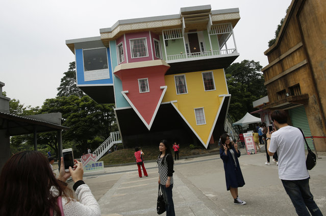 Visitors pose in front of a three story upside-down family sized house at the Huashan Creative Park in Taipei, Taiwan. Over 300 square meters of floor space of the upside-down house, filled with home furnishings, was created by a group of Taiwanese architects at a total cost of around US$600,000 and took 2 months to complete, according to the organisers. (Photo by Tyrone Siu/Reuters)