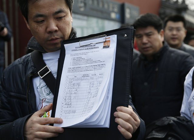 A family member of passengers onboard the missing Malaysia Airlines flight MH370, shows the petition to appeal for the continuation of search efforts for the missing which the family members signed, outside Yonghegong Lama Temple after a gathering of family members of the missing passengers in Beijing March 8, 2015. Prime Minister Najib Razak said on Sunday Malaysia remains committed to the search for the missing MH370 jetliner a year after it vanished without trace and he is hopeful it will be found.