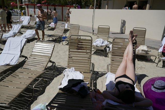 Visitor Rachel Baudek sunbathes by the pool as tourists flock to Las Vegas ahead of Memorial Day weekend at Mandalay Bay hotel and casino in Las Vegas, Nevada, U.S., May 28, 2021. (Photo by Bridget Bennett/Reuters)
