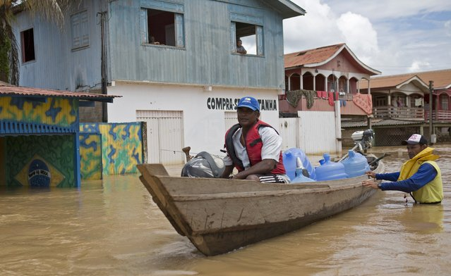 A man navigates with containers of potable water in his boat in a neighbourhood flooded by the Purus river, which continues to rise from days of heavy rainfall in the region, in Boca do Acre, Amazonas state March 14, 2015. (Photo by Bruno Kelly/Reuters)