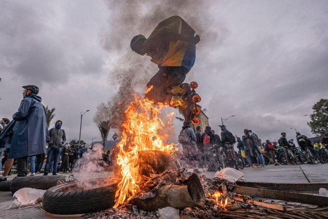 A demonstrator in roller skates wearing a Colombian flag on his back jumps over a bonfire during national strike on May 5, 2021 in Bogota, Colombia. Despite that the ruling party announced withdrawal of the unpopular bill for a tax reform and the resignation of the Minister of Finances, social unrest continues after a week. The United Nations human rights office (OHCHR) showed its concern and condemned the riot police repression. Ongoing protests take place in major cities since April 28. (Photo by Diego Cuevas/Getty Images)
