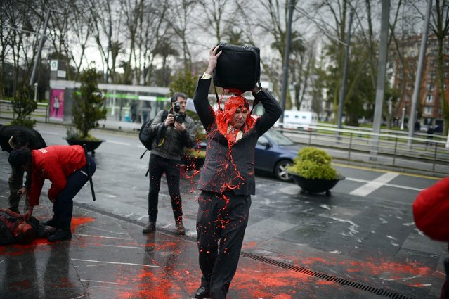 A protester covers himself in red paint before the Annual General Shareholders Meeting of Spain's second biggest bank BBVA at the Palacio Euskalduna in Bilbao March 13, 2015. The protesters, who shouted slogans, are against what they say is the bank's relationship to the defence industry. (Photo by Vincent West/Reuters)