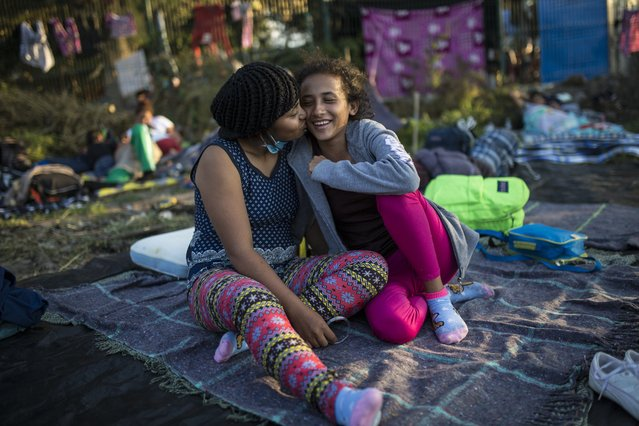 Central American migrants, Genesis Cruz, 18, left, and her girlfriend, Lourdes Ramirez, 18, from Honduras, kisses while relaxing in a makeshift shelter in Irapuato, Mexico, Sunday, November 11, 2018. (Photo by Rodrigo Abd/AP Photo)
