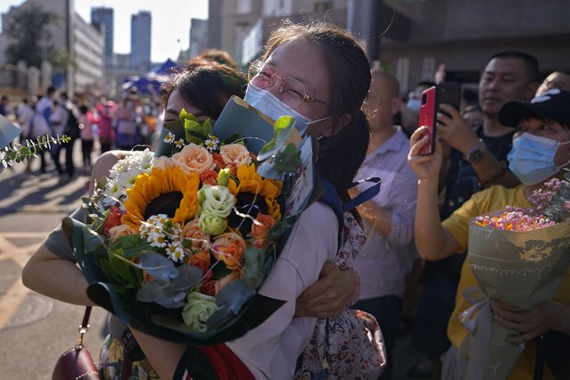 A student wearing a face mask to help curb the spread of the coronavirus with a bouquet of flowers is hugged by her relative at the end of China's national college entrance examinations, known as the gaokao in Beijing, Thursday, June 10, 2021. Millions of students took part in the tough annual exams from which the results determine entrance to the country's top universities. (Photo by Andy Wong/AP Photo)