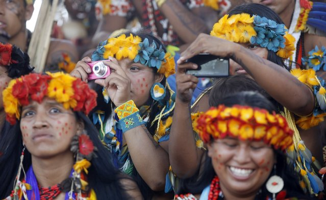 Members of indigenous group Paresi take photographs during the XII Games of the Indigenous People in Cuiaba November 10, 2013. (Photo by Paulo Whitaker/Reuters)