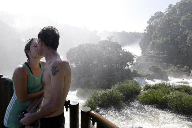 In this March 14, 2015 photo, Brazilians Lilian and Edgardo kiss in the spray of Iguazu Falls in Brazil. Local indigenous legend has it that serpent god Boi, furious over a broken heart, created the falls by shattering the Iguazu river's flow to prevent the maiden Naipu from escaping in a canoe with her lover Taroba. The legend says the rainbows that grace the waters are the souls of Naipu and Taroba reuniting. (Photo by Jorge Saenz/AP Photo)