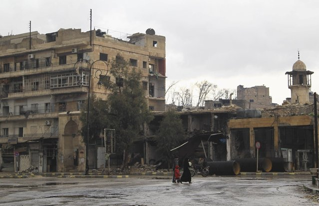 Civilians walk along a deserted street in the old city of Aleppo January 6, 2015. (Photo by Jalal Al-Mamo/Reuters)