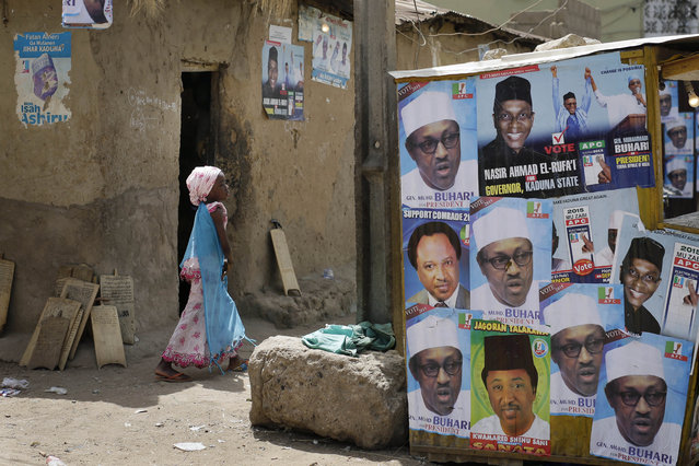 A young Nigerian girl walks past election posters, some showing presidential candidate, Muhammadu Buhari, in Kaduna, Nigeria Monday, March 30, 2015. (Photo by Jerome Delay/AP Photo)