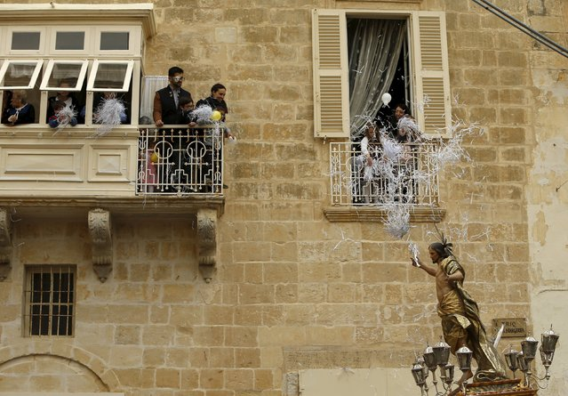People in balconies throw confetti over a statue of the Risen Christ during an Easter Sunday procession in Cospicua, outside Valletta April 5, 2015. (Photo by Darrin Zammit Lupi/Reuters)