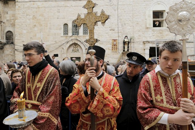 Members of the Greek Orthodox clergy await the arrival of the Greek Orthodox Patriarch of Jerusalem Metropolitan Theophilos before the washing of the feet ceremony outside the Church of the Holy Sepulchre in Jerusalem's Old City, April 9, 2015, ahead of Orthodox Easter. (Photo by Ammar Awad/Reuters)