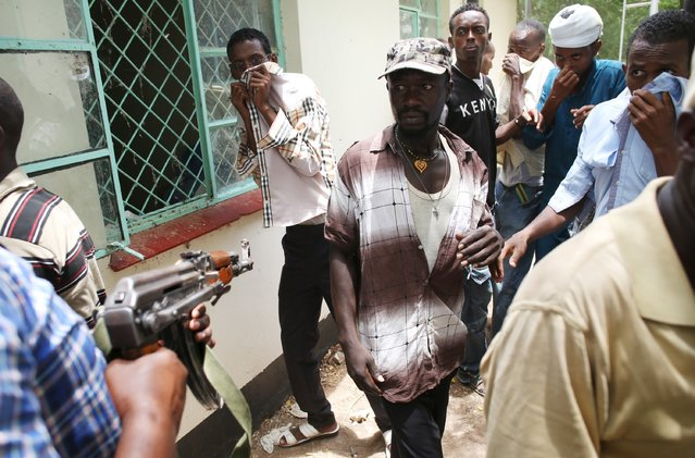 A policeman points his gun as he tries to push back people who came to see the bodies of suspected Garissa University College attackers in a morgue in Garissa April 4, 2015. (Photo by Goran Tomasevic/Reuters)