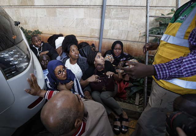 Civilians huddle between cars as the sound of gunshots are heard at a hotel complex in Nairobi, Kenya Tuesday, January 15, 2019. Terrorists attacked an upscale hotel complex in Kenya's capital Tuesday, sending people fleeing in panic as explosions and heavy gunfire reverberated through the neighborhood. (Photo by Ben Curtis/AP Photo)