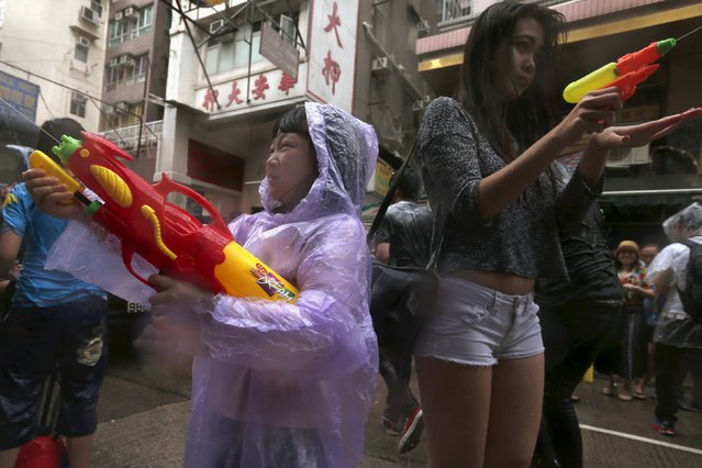 Revellers use water guns as they participate in a water fight during Songkran Festival celebrations at Kowloon City district, known as Little Thailand as there is large number of restaurants and shops run by Thais, in Hong Kong April 12, 2015. (Photo by Tyrone Siu/Reuters)
