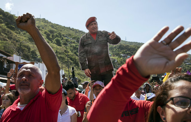 Government supporters hold a life-size image of Venezuela's late President Hugo Chavez during a rally in La Guaira, Venezuela, Friday, January 25, 2019. Venezuelan President Nicolas Maduro, Chavez's protege, says he's willing to engage in talks with the opposition in order to avoid violence in a conflict over who is the legitimate leader of the country. (Photo by Rodrigo Abd/AP Photo)
