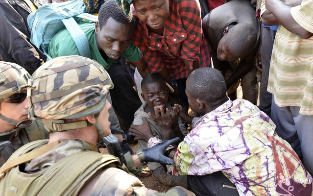 French troops of the Sangaris operation and civilians try to comfort a boy crying after a demonstrator was shot dead near the international airport in Bangui on December 23, 2013. African Union troops fired on demonstrators protesting against the president of the strife-torn Central African Republic, killing at least one person, according to AFP reporters on the scene. (Photo by Miguel Medina/AFP Photo)