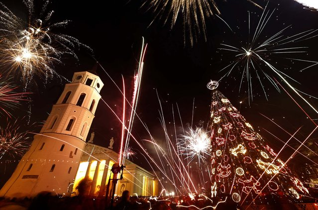 Fireworks light the sky above Cathedral Square in Vilnius, Lithuania. (Photo by Mindaugas Kulbis/Associated Press)