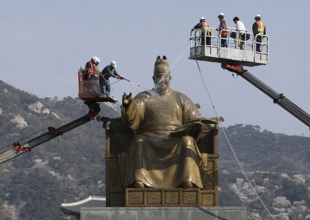Workers clean the bronze statue of King Sejong at Gwanghwamun Plaza in Seoul, South Korea, Monday, April 13, 2015, King Sejong, the fourth king of the Joseon Dynasty (1392-1910), created the Korean alphabet, hangeul, in 1446. (Photo by Ahn Young-joon/AP Photo)