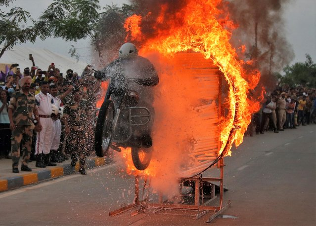 A Border Security Force (BSF) trooper performs a stunt on his motorcycle during a road show to celebrate 75 years of India's Independence, in Ahmedabad, India, August 25, 2021. (Photo by Amit Dave/Reuters)