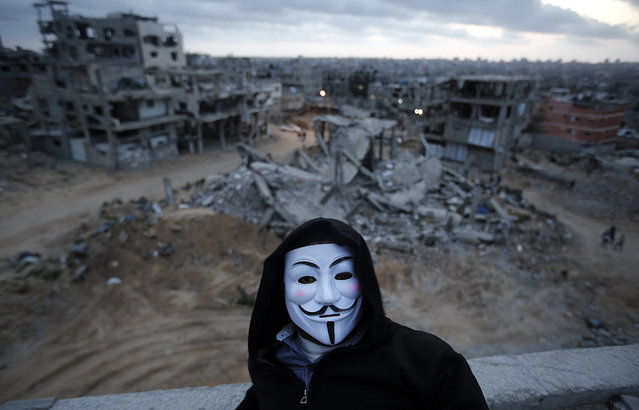 A picture made available on 16 April 2015 shows a Palestinian guy wearing a Vendetta mask as he sits on the roof of his destroyed house, which was damaged during the 2014 Israel-Gaza conflict, in Al Shejaeiya neighbourhood, in the east of Gaza City, Gaza Strip, 15 April 2015. (Photo by Mohammed Saber/EPA)
