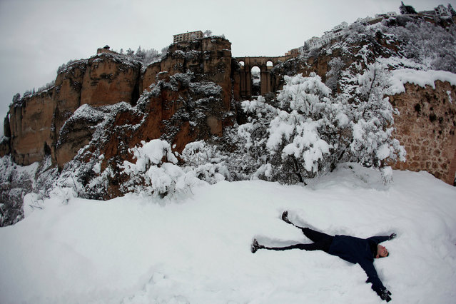 """A man makes a snow angel in front of the """"Puente Nuevo"""" (New Bridge) during a snowfall in Ronda, near Malaga, Spain January 19, 2017. (Photo by Jon Nazca/Reuters)"""