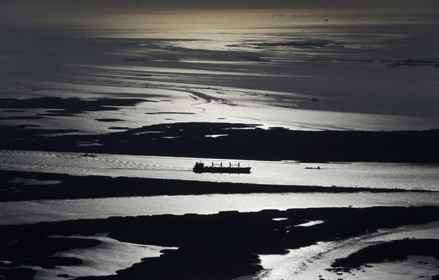 In this Tuesday, March 31, 2015 aerial photo, a cargo ship plies up the Mississippi River towards New Orleans in Plaquemines Parish, La. (Photo by Gerald Herbert/AP Photo)