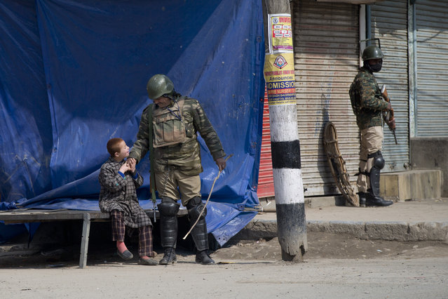 An Indian paramilitary soldier plays with a Kashmiri child as he stands guard during security lockdown in Srinagar, Indian controlled Kashmir, Sunday, Februaary 24, 2019. Shops and businesses have closed in Kashmir to protest a sweeping crackdown against activists seeking the end of Indian rule in the disputed region. (Photo by Dar Yasin/AP Photo)