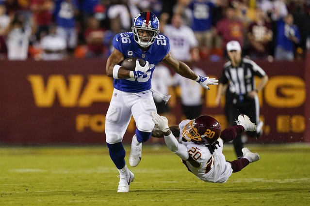 New York Giants running back Saquon Barkley (26) breaks away from Washington Football Team cornerback Bobby McCain (20) as he runs with the ball during the first half of an NFL football game, Thursday, September 16, 2021, in Landover, Md. (Photo by Alex Brandon/AP Photo)