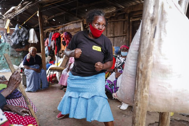 """Group leader Jane Waithageni Kimaru, 60 years old, strikes a punching bag to show women how to fight off a potential rapist and escape, during a Taekwondo self-defense class for women in the Korogocho slum of Nairobi, Kenya, Thursday, September 16, 2021. In Korogocho, which means """"crowded shoulder to shoulder"""" in Swahili, the women meet every week to train in skills they hope can help them fight back if they are sexually assaulted. (Photo by Brian Inganga/AP Photo)"""