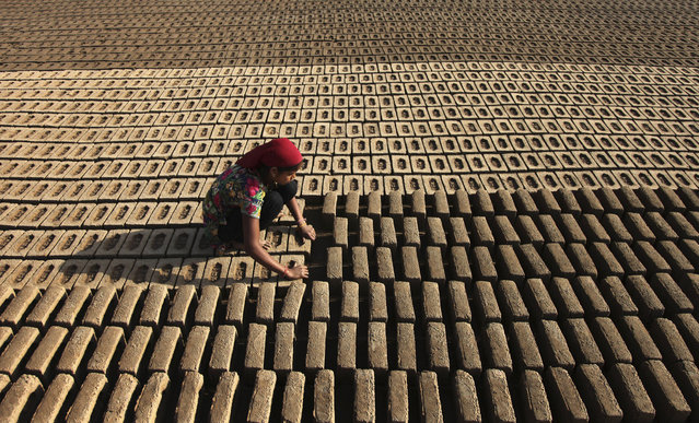 An Indian woman laborer works at an earthen brick factory on Earth Day on the outskirts of Jammu, India, Wednesday, April 22, 2015. (Photo by Channi Anand/AP Photo)