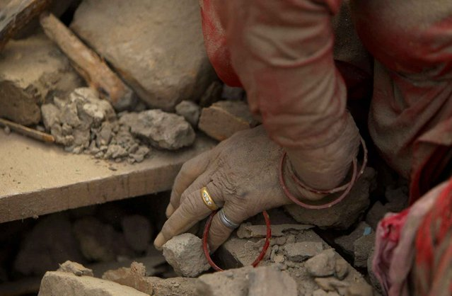 The hand of a dead woman is seen after rescue workers recovered it from debris in Bhaktapur near Kathmandu, Nepal, Sunday, April 26, 2015. (Photo by Niranjan Shrestha/AP Photo)