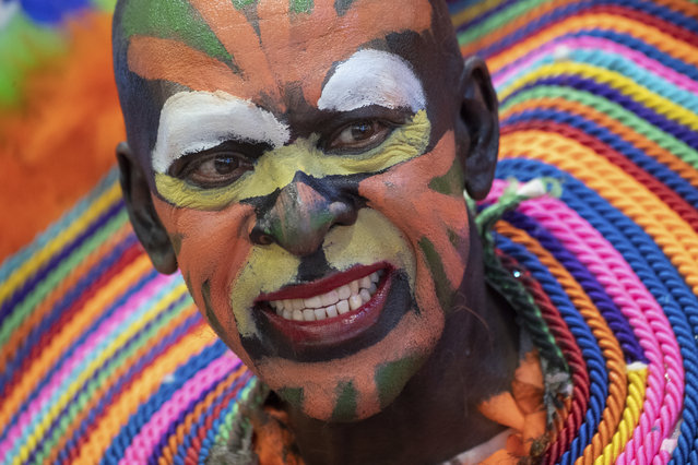 A man with a colorful painted face promotes traveling to the Dominican Republic at the ITB tourism fair in Berlin, Germany, Friday, March 8, 2019. (Photo by Ralf Hirschberger/dpa via AP Photo)