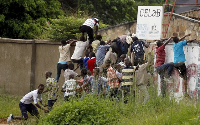 Residents attempt to scale a wall as they run from riot policemen during street protests against the decision made by Burundi's ruling National Council for the Defence of Democracy-Forces for the Defence of Democracy (CNDD-FDD) party to allow President Pierre Nkurunziza to run for a third five-year term in office, in the capital Bujumbura, April 26, 2015. (Photo by Thomas Mukoya/Reuters)