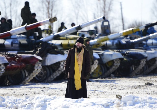 A priest walks in front of a line of tanks ahead of an individual race at a regional stage of the 2016 Tank Biathlon Competition at the Anastasyevsky training ground, March 1, 2016, Khabarovsk Territory, Russia. (Photo by Yuri Smityuk/TASS/Newscom)