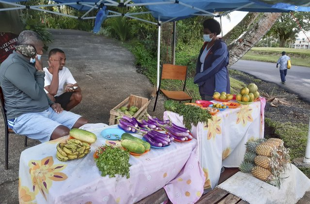 A family sells produce in front of their home in Suva, Fiji, Thursday, June 24, 2021. Mosese Soro, left, had to give up his business buying and selling fish because it can't operate while Fiji's borders are closed due to COVID restrictions. (Photo by Aileen Torres-Bennett/AP Photo)