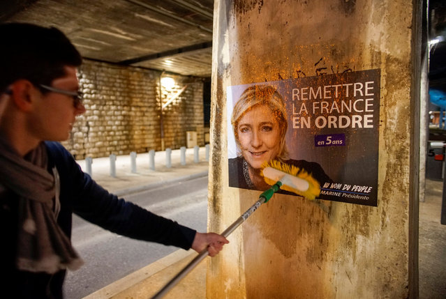 A member of the National Front youths puts up a poster of Marine Le Pen, French National Front (FN) political party leader and candidate for the French 2017 presidential election, ahead of a 2-day FN political rally to launch the presidential campaign in Lyon, France, February 2, 2017. (Photo by Robert Pratta/Reuters)