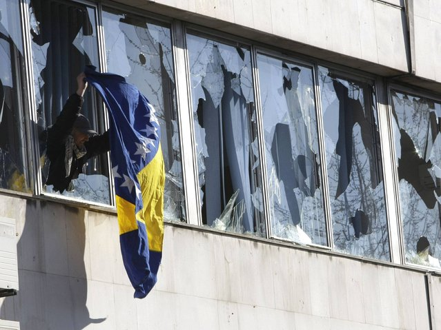 A Bosnian flag hangs from a broken window of a local government building, during protests in the Bosnian town of Tuzla, on Friday, February 7, 2014. (Photo by Amel Emric/AP Photo)