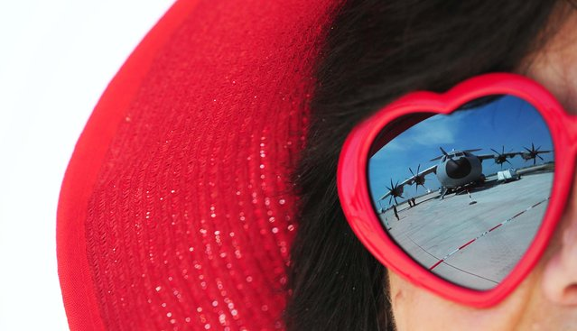 A military plane is reflected in the heart-shaped sunglasses of a spectator at the International Aerospace Exhibition at the Schoenefeld airport in Berlin. (Photo by Johannes Eisele/AFP Photo)