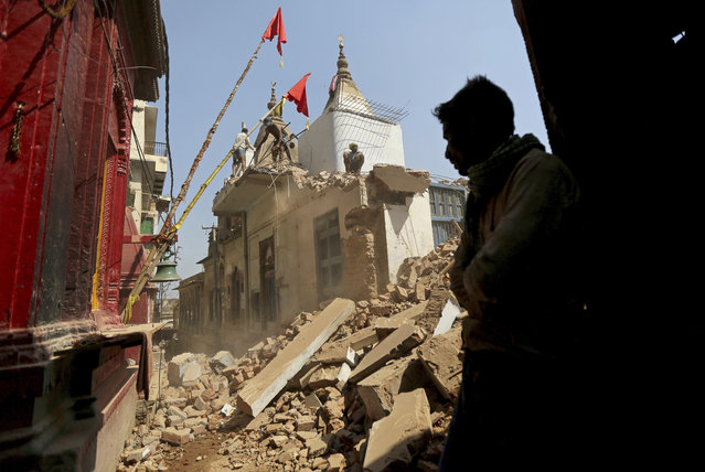 In this March 19, 2019, photo, workers demolish a house at the site of a proposed grand promenade connecting the sacred Ganges river with a centuries-old temple dedicated to Lord Shiva, in Varanasi, India. A project in the ancient Indian city of Varanasi dreamed up by Prime Minister Narendra Modi shows the master political marketer's penchant for symbolism as political strategy in elections that begin this month. (Photo by Altaf Qadri/AP Photo)